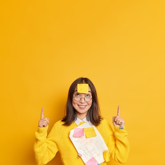 Positieve succesvolle vrouwelijke manager in casual trui met papieren en stickers geplakt door paperclips glimlacht en punten op kopie ruimte