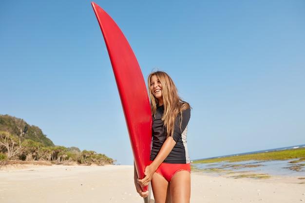 Positieve surfer draagt een rode bikini