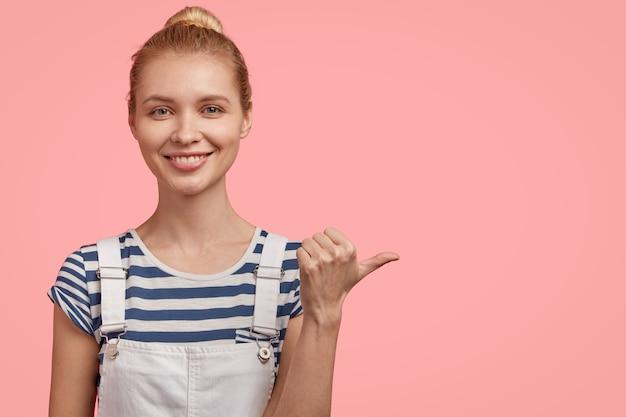 Positieve tevreden blonde vrouw met gekamd haar, draagt een gestreept t-shirt en denim overall, wijst met duim opzij, lacht aangenaam, toont vrije ruimte rechts geïsoleerd over roze muur