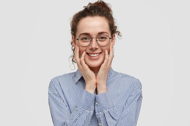 Positieve tevreden jonge vrouw heeft een zachte glimlach, raakt wangen met handen