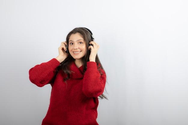 Positieve tiener luistert naar muziek in stereohoofdtelefoons.