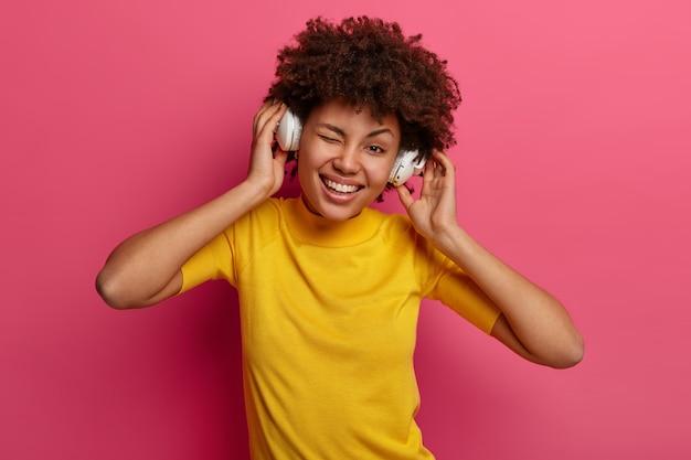 Positieve tiener met krullend haar knipoogt, glimlacht gelukkig terwijl hij naar muziek luistert in een stereohoofdtelefoon, voelt zich geamuseerd, kantelt het hoofd, geniet van mooi geluid, draagt een geel t-shirt, poseert tegen een roze muur