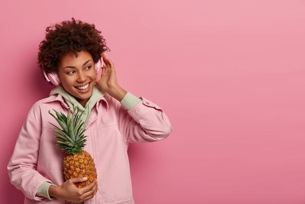 Positieve tienermeisje luistert naar muziek, draagt een koptelefoon op de oren, voelt zich erg blij, houdt rijpe ananas vast, kijkt opzij van geluk, draagt casual kleding, geïsoleerd over roze muur, lege ruimte voor promo