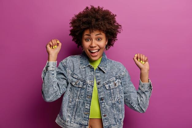 Positieve tienermeisje met natuurlijk krullend haar armen omhoog, gebalde vuisten, heeft een opgewekte stemming, verheugt zich over succes, draagt spijkerjasje, geïsoleerd over paarse muur, danst op favoriete muziek op feestje