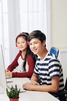 Positieve tieners die op computers werken