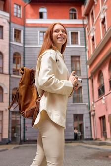 Positieve toeristische roodharige vrouw die foto's maakt van architectuur op retro filmcamera die op straat staat...
