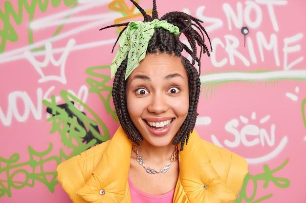 Positieve trendy jongvolwassene behoort tot de jeugdsubcultuur die een gemeenschappelijke kledingstijl en -gedrag heeft, draagt een geel vest, heeft een blije blik op camerahoudingen tegen de graffitimuur verbaasd