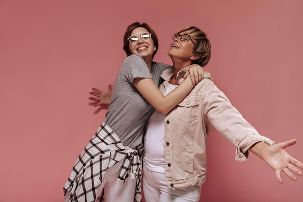 Positieve twee kortharige vrouwen met moderne bril in modieuze lichte kleding knuffelen en glimlachen op roze achtergrond.