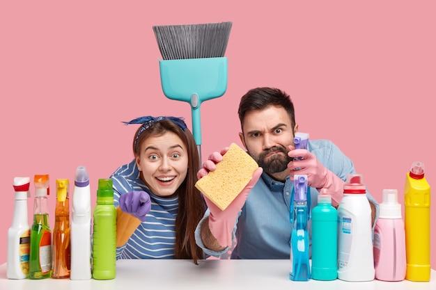 Positieve twee mensen kijken nauwgezet naar de camera, houden bezem en spons vast, zitten aan het bureaublad met schoonmaakspullen