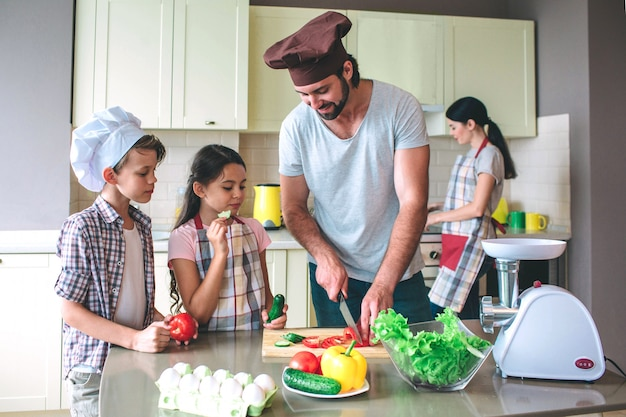 Positieve vader snijdt tomaat met mes. meisje houdt komkommer en eet het. jongen heeft tomaat in handen
