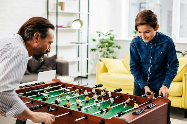 Positieve vader tijd doorbrengen met zijn zoon thuis en genieten van het spelen van tafelvoetbal in de woonkamer met hem