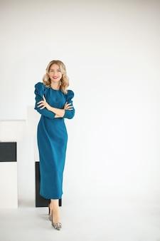 Positieve vertrouwen stijlvolle 30s jonge mooie vrouwelijke zakenvrouw in blauwe jurk poseren op witte studio.