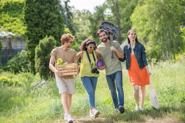 Positieve vibes. vier gelukkige jonge vrienden met gitaarcamera en bal wandelen in het park voor een picknick op fijne middag