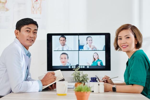 Positieve vietnamese medische hulpverleners die aantekeningen maken tijdens een online ontmoeting met collega's uit andere ziekenhuizen
