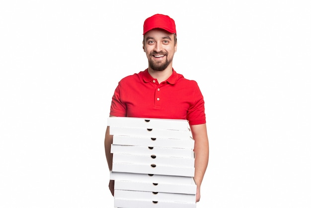 Positieve volwassen bebaarde koerier in rood uniform met stapel kartonnen pizzadozen en kijkt met een vriendelijke glimlach