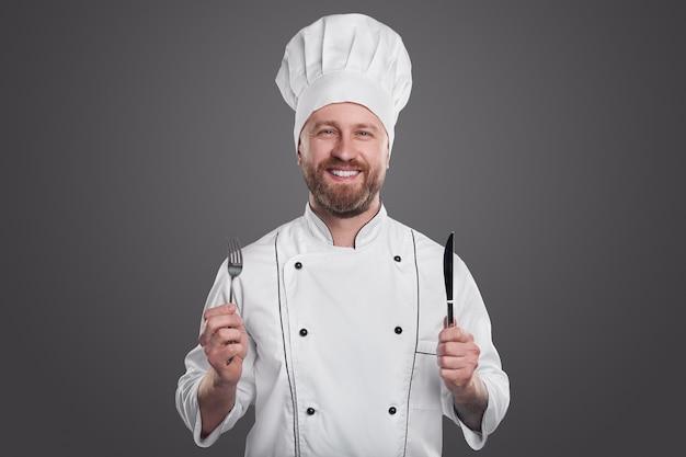 Positieve volwassen bebaarde mannelijke chef-kok in wit uniform met vork en mes en camera kijken terwijl het vertegenwoordigen van restaurantservice tegen een grijze achtergrond