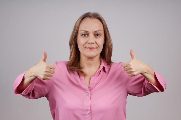 Positieve volwassen dame met roze blouse verschijnt duimen. studio die over grijze achtergrond met exemplaarruimte is ontsproten.