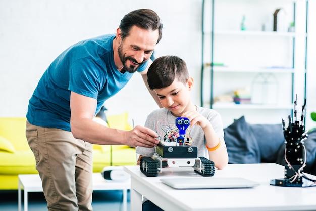 Positieve volwassen man die zijn zoon helpt met robottechniek tijdens het testen van zijn creatie