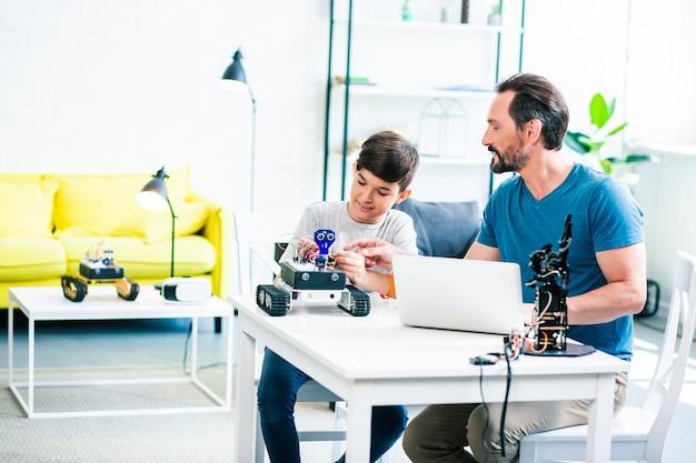 Positieve volwassen man en zijn zoon zitten aan tafel tijdens het experimenteren met robot