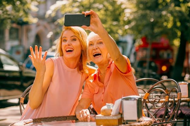 Positieve volwassen moeder en dochter die buiten zitten en selfies nemen