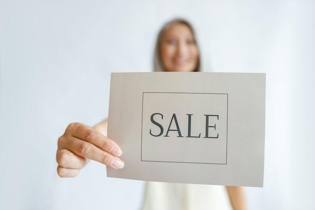 Positieve volwassen vrouw staat in studio, focus op hand met kaart met woord sale