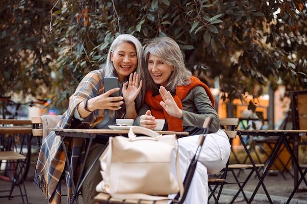 Positieve volwassen vrouwenvrienden zwaaien met de hand naar videochat via smartphone in straatcafé