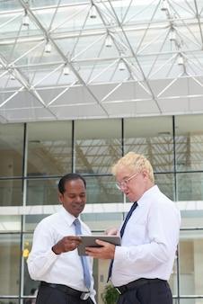 Positieve volwassen zakenmensen die in de hal van het kantoorgebouw staan