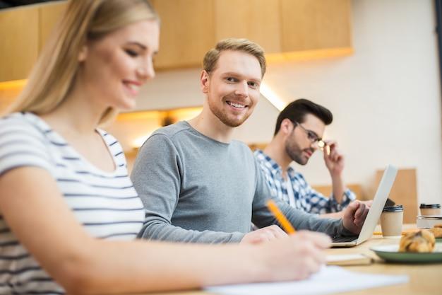 Positieve vreugdevolle jonge student die samen zit en studeert tijdens de voorbereiding op hun examens