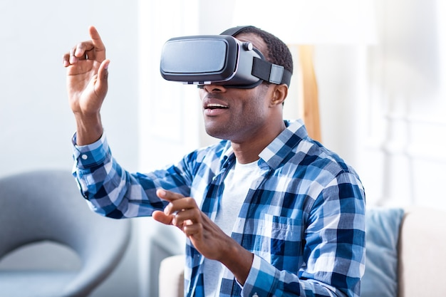 Positieve vreugdevolle opgewonden man met virtual reality-bril en glimlachen tijdens het testen van nieuwe technologie