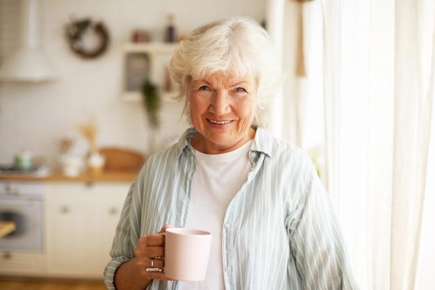 Positieve, vriendelijk ogende senior bejaarde vrouw met grijs haar en rimpels die de dag thuis doorbrengen, 's ochtends thee of koffie drinken