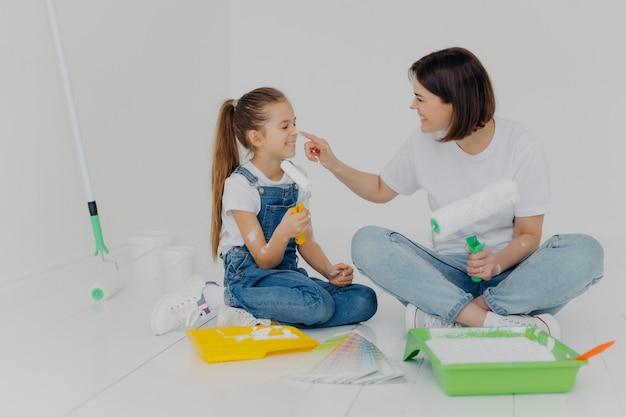 Positieve vriendelijke moeder en dochter smeren elkaar met witte verf