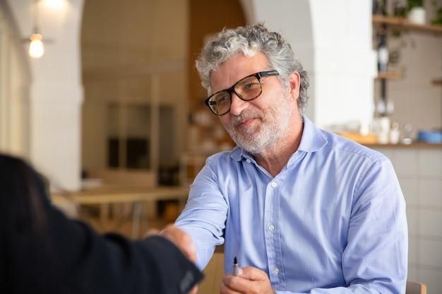 Positieve vriendelijke zakenman in glazen handen schudden met partner tijdens bijeenkomst
