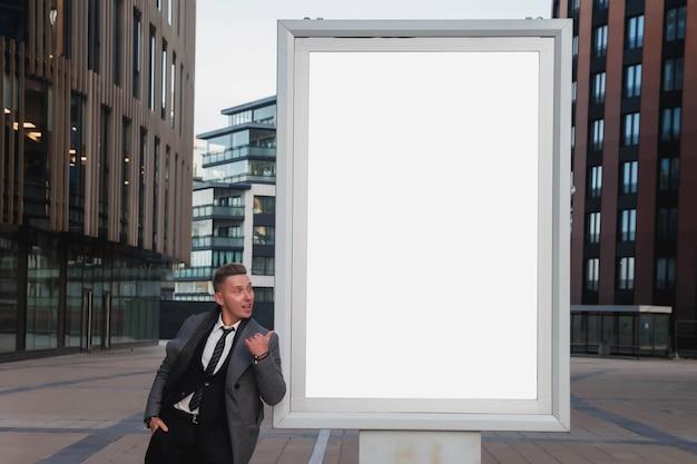 Positieve vriendelijke zakenman voor presentatie of reclame voor product, merk, logo op website of poster. knappe jonge man in pak op een leeg reclamebord tegen de achtergrond van zakelijke gebouw