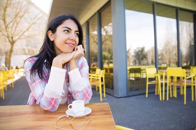Positieve vrij jonge dame die van het drinken van koffie in koffie geniet