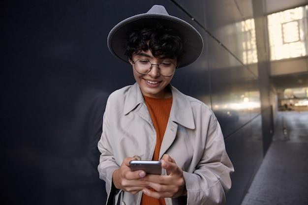 Positieve vrij krullend vrouw met kort kapsel smartphone in handen houden en chatten met haar vrienden, staande boven de stad in trendy outfit