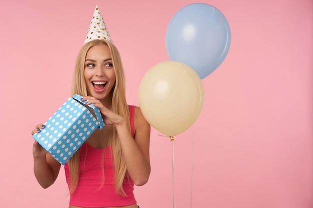 Positieve vrij langharige blonde dame met casual kapsel toont haar aangename emoties tijdens het openen van een geschenkdoos, opzij kijkend met een brede, gelukkige glimlach, staande over roze achtergrond