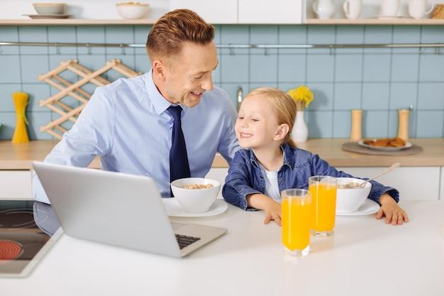 Positieve vrolijke aardige meid die op het laptopscherm kijkt en lacht tijdens het ontbijt samen met haar vader