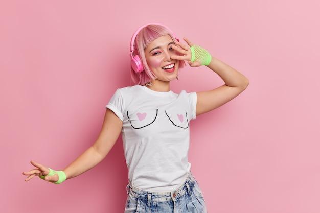 Positieve vrolijke aziatische tienermeisje voelt zorgeloze bewegingen met het ritme van muziek