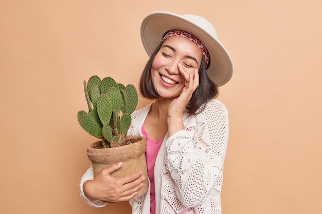 Positieve vrolijke aziatische vrouw kantelt hoofd glimlacht breed houdt ogen gesloten