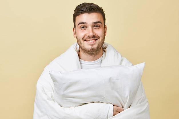 Positieve vrolijke jongeman met schattige glimlach en ongeschoren gezicht staande op een blinde muur, gewikkeld in een witte deken, zich dolgelukkig voelen, herstellende van de kou, kussen vasthoudend, in bed gaan slapen