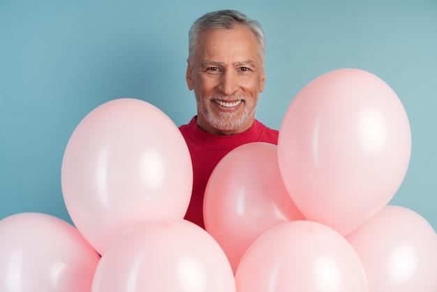 Positieve, vrolijke man met ballonnen die zich voordeed op blauwe muurmuur