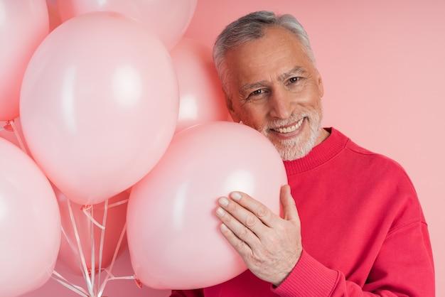 Positieve, vrolijke man met ballonnen die zich voordeed op roze muurmuur