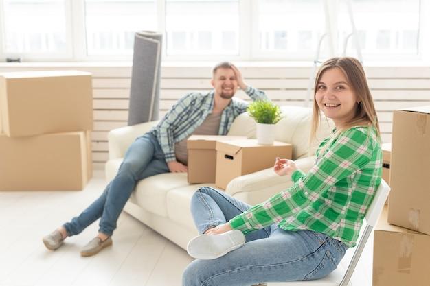 Positieve vrolijke paar verheugt zich in het verplaatsen van hun nieuwe appartement zittend in de woonkamer met
