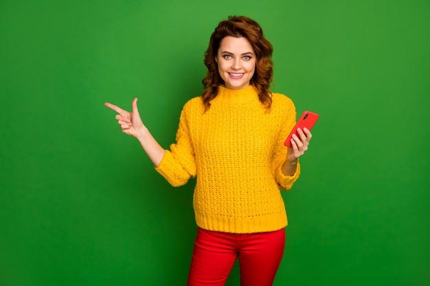 Positieve vrolijke promotor punt wijsvinger copyspace geven social media advertenties promotie gebruik smartphone dragen stijlvolle trui broek geïsoleerde heldere glans kleur muur