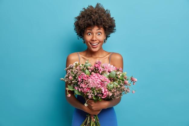 Positieve vrolijke schattige afro-amerikaanse vrouw glimlacht breed en houdt een groot bezorgboeket met mooie bloemen vast