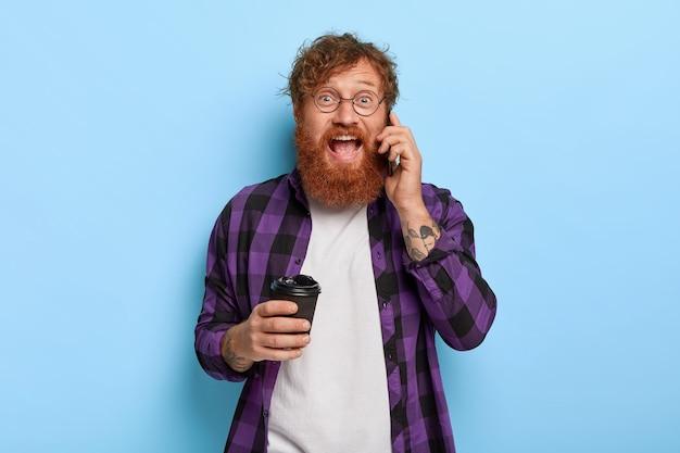 Positieve vrolijke stijlvolle gember man poseren tegen de blauwe muur