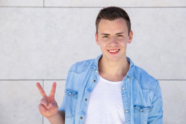 Positieve vrolijke studentenkerel die vredesteken maken