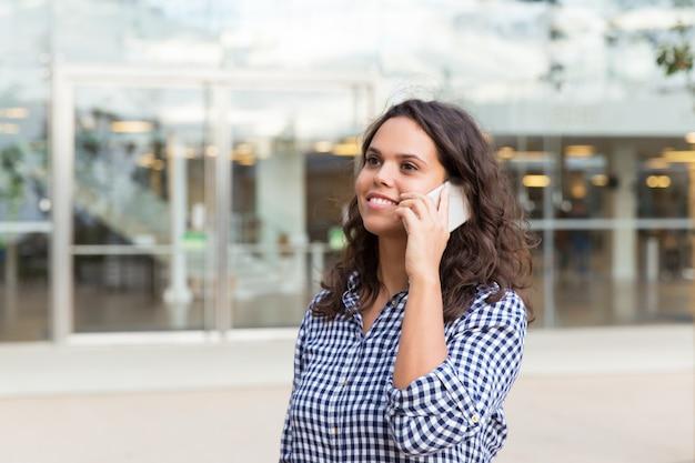 Positieve vrolijke vrouw die op mobiele telefoon spreekt