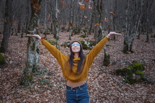 Positieve vrolijke vrouw geniet van de herfst in park of bos, draag gele trui en hoed, bril. stemming gelukkig hipster meisje in de late herfst bos road trip