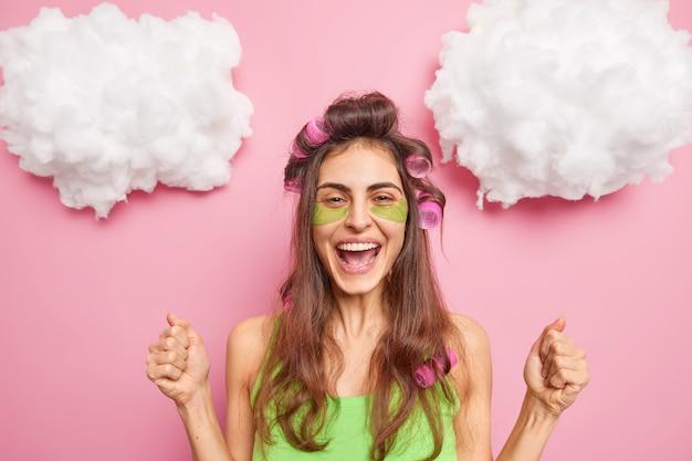 Positieve vrouw balt vuisten viert iets past haarrollers groene schoonheid patches onder de ogen wil een geweldig kapsel morgen traktaties zichzelf geïsoleerd op roze muur